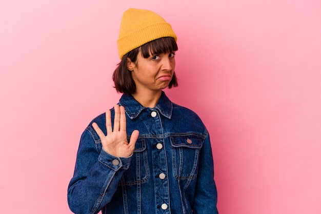 Mulher jovem de raça mista isolada em fundo rosa rejeitando alguém mostrando um gesto de nojo.