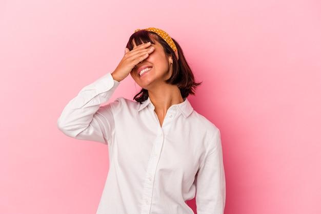 Mulher jovem de raça mista isolada em fundo rosa ri com alegria, mantendo as mãos na cabeça. conceito de felicidade.