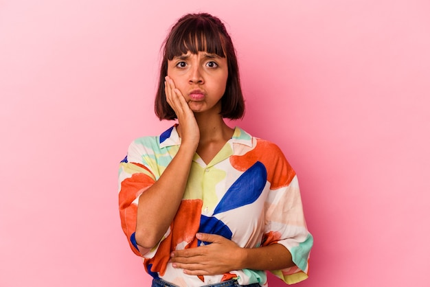 Mulher jovem de raça mista isolada em fundo rosa sopra nas bochechas, tem expressão cansada. conceito de expressão facial.
