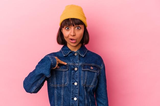 Mulher jovem de raça mista isolada em fundo rosa surpresa apontando com o dedo, sorrindo amplamente.
