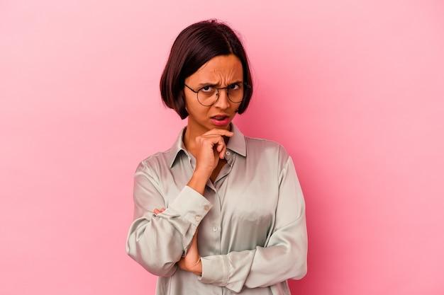 Mulher jovem de raça mista isolada em fundo rosa suspeita, incerta, examinando você.
