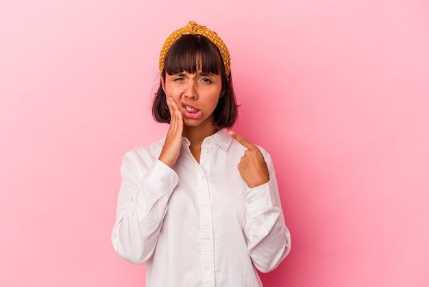 Mulher jovem de raça mista isolada em fundo rosa, tendo uma forte dor nos dentes, dor molar.