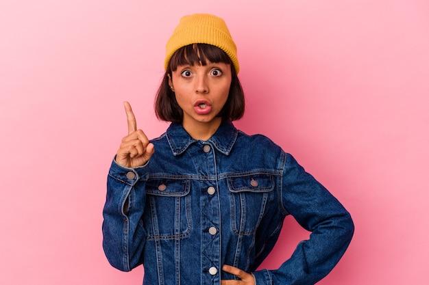 Mulher jovem de raça mista isolada em fundo rosa, tendo uma ideia, o conceito de inspiração.