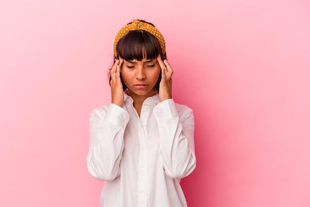 Mulher jovem de raça mista isolada em fundo rosa, tocando as têmporas e tendo dor de cabeça.