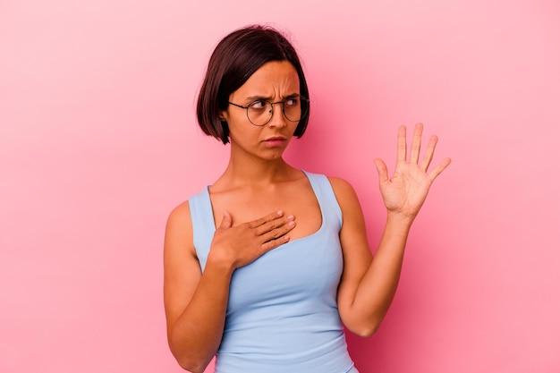 Mulher jovem de raça mista isolada em rosa, fazendo um juramento, colocando a mão no peito.