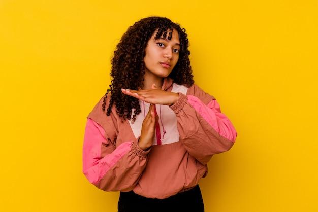 Mulher jovem de raça mista isolada em rosa, mostrando um gesto de tempo limite.
