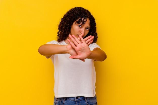 Mulher jovem de raça mista isolada em um fundo amarelo em pé com a mão estendida, mostrando o sinal de stop, impedindo-o.