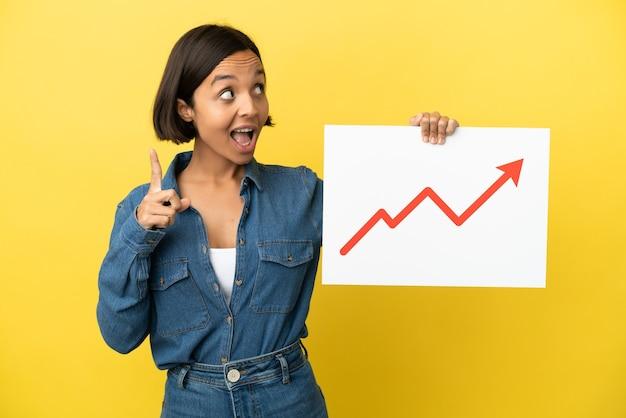 Mulher jovem de raça mista isolada em um fundo amarelo segurando uma placa com estatísticas crescentes