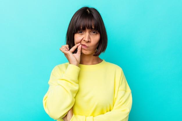 Mulher jovem de raça mista isolada em um fundo azul com os dedos nos lábios, mantendo um segredo.