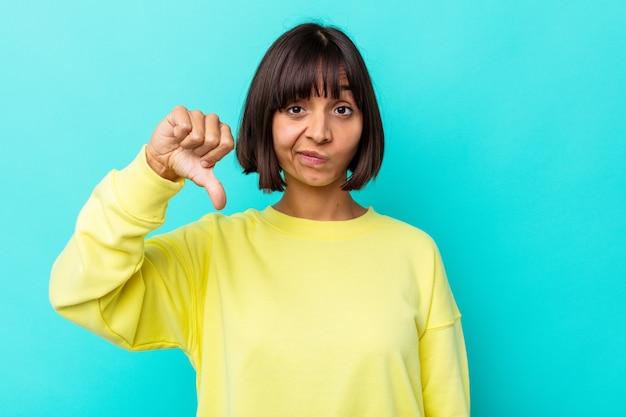 Mulher jovem de raça mista isolada em um fundo azul, mostrando o polegar para baixo, o conceito de decepção.