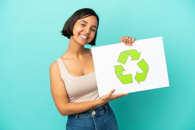 Mulher jovem de raça mista isolada em um fundo azul segurando um cartaz com o ícone de reciclagem e uma expressão feliz