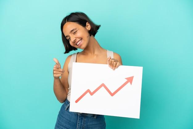 Mulher jovem de raça mista isolada em um fundo azul segurando uma placa com um símbolo de seta de estatísticas crescentes e apontando para a frente