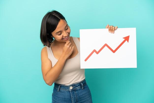 Mulher jovem de raça mista isolada em um fundo azul segurando uma placa com um símbolo de seta de estatísticas crescentes e pensando