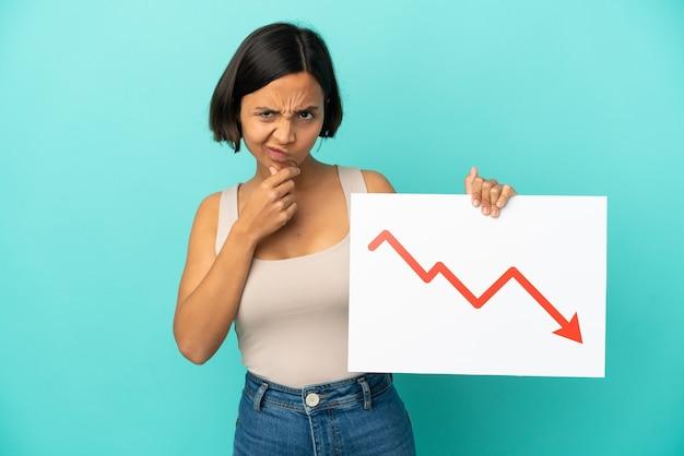Mulher jovem de raça mista isolada em um fundo azul segurando uma placa com um símbolo de seta decrescente de estatísticas e pensando