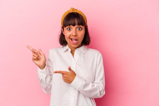 Mulher jovem de raça mista isolada em um fundo rosa animado apontando com os dedos indicadores de distância.