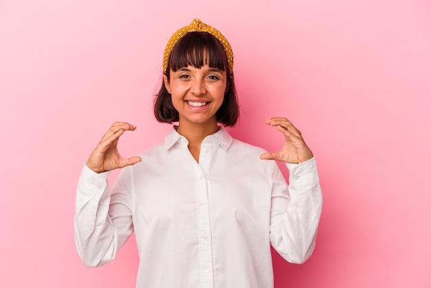 Mulher jovem de raça mista isolada em um fundo rosa segurando algo com as palmas das mãos, oferecendo-se para a câmera.