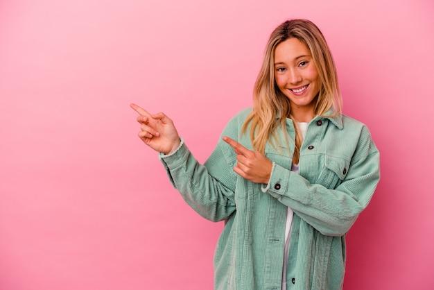 Mulher jovem de raça mista isolada na parede rosa chocada apontando com o dedo indicador para um espaço de cópia.