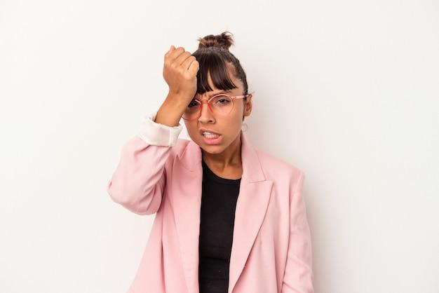Mulher jovem de raça mista isolada no fundo branco, esquecendo algo, batendo na testa com a palma da mão e fechando os olhos.