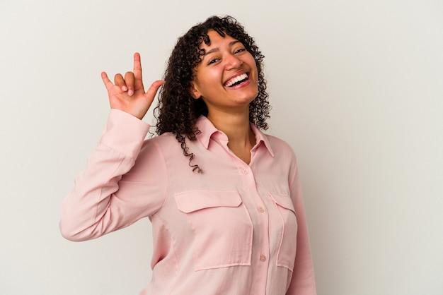 Mulher jovem de raça mista isolada no fundo branco, mostrando um gesto de chifres como um conceito de revolução.