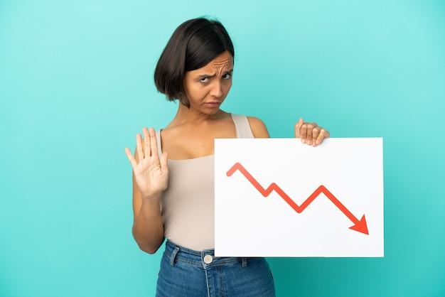 Mulher jovem de raça mista isolada segurando uma placa com um símbolo de seta de estatísticas decrescentes e fazendo o sinal de pare