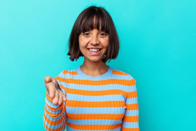 Mulher jovem de raça mista isolada sobre fundo azul, esticando a mão na câmera em gesto de saudação.