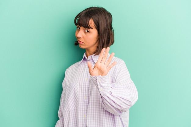 Mulher jovem de raça mista isolada sobre fundo azul, rindo de algo, cobrindo a boca com as mãos.