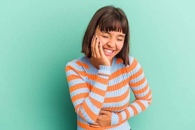 Mulher jovem de raça mista isolada sobre fundo azul, rindo e se divertindo.
