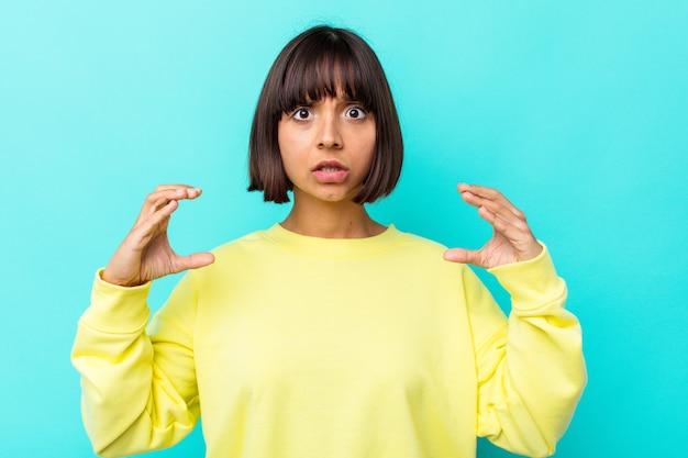 Mulher jovem de raça mista isolada sobre fundo azul, segurando algo com as palmas das mãos, oferecendo-se para a câmera.