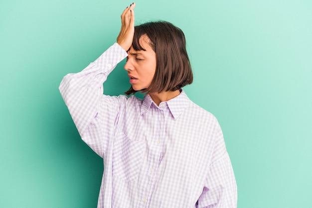 Mulher jovem de raça mista isolada sobre fundo azul, tentando ouvir uma fofoca.