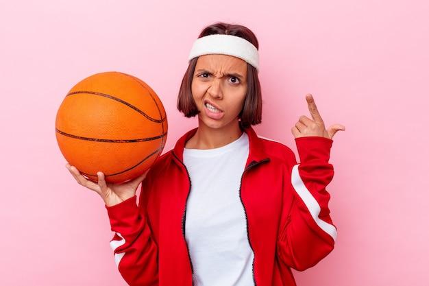 Mulher jovem de raça mista jogando basquete, isolado em um fundo rosa, mostrando um gesto de decepção com o dedo indicador.