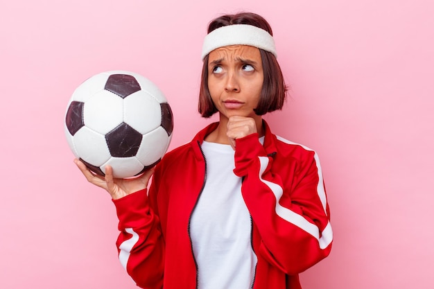 Mulher jovem de raça mista jogando futebol isolada na parede rosa, olhando de soslaio com expressão duvidosa e cética.