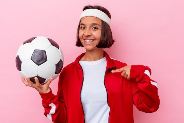 Mulher jovem de raça mista jogando futebol isolada na parede rosa pessoa apontando com a mão para um espaço de cópia de camisa, orgulhosa e confiante