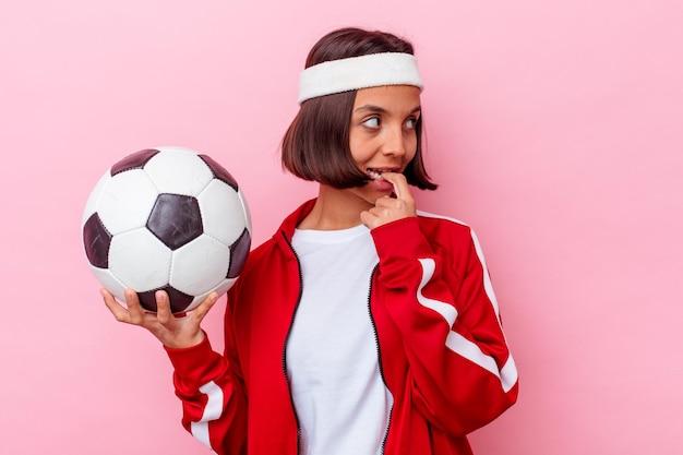 Mulher jovem de raça mista jogando futebol isolada na parede rosa relaxada pensando em algo olhando para um espaço de cópia.