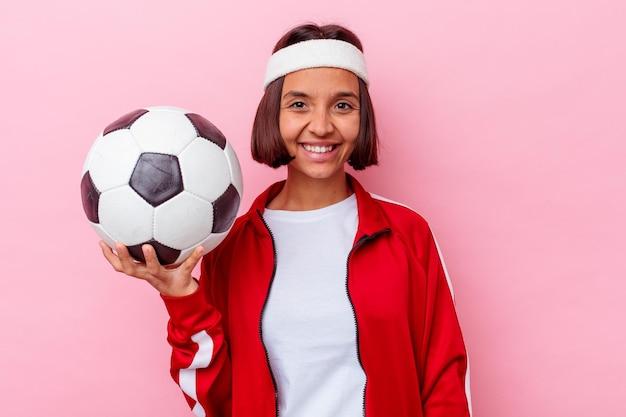 Mulher jovem de raça mista jogando futebol isolado na parede rosa feliz, sorridente e alegre.