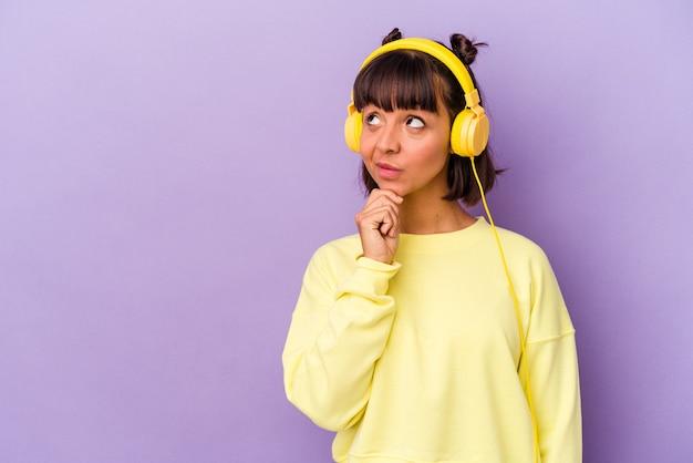 Mulher jovem de raça mista, ouvindo música isolada em fundo roxo, olhando de soslaio com expressão duvidosa e cética.