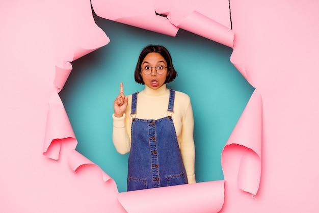 Mulher jovem de raça mista por trás de um fundo quebrado, mostrando um gesto de chifres como um conceito de revolução.