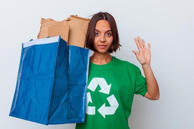 Mulher jovem de raça mista, reciclando papelão isolado na parede branca, sorrindo alegre mostrando o número cinco com os dedos.