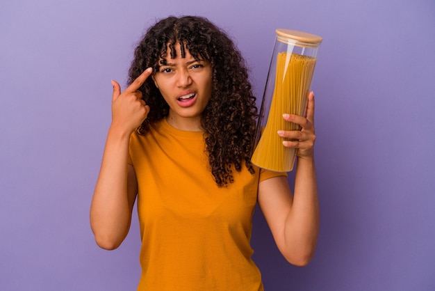 Mulher jovem de raça mista segurando espaguete isolado na parede roxa, mostrando um gesto de decepção com o dedo indicador.