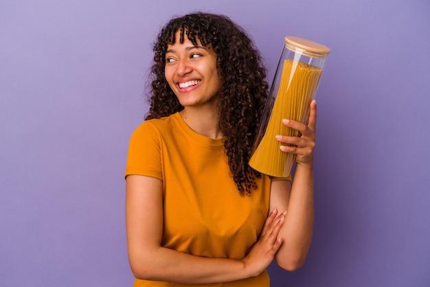Mulher jovem de raça mista segurando espaguete isolado na parede roxa, rindo e se divertindo.