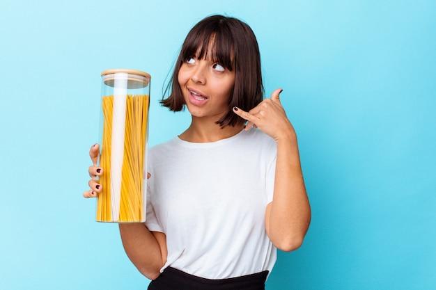 Mulher jovem de raça mista segurando o frasco de macarrão isolado em um fundo azul, mostrando um gesto de chamada de telefone móvel com os dedos.