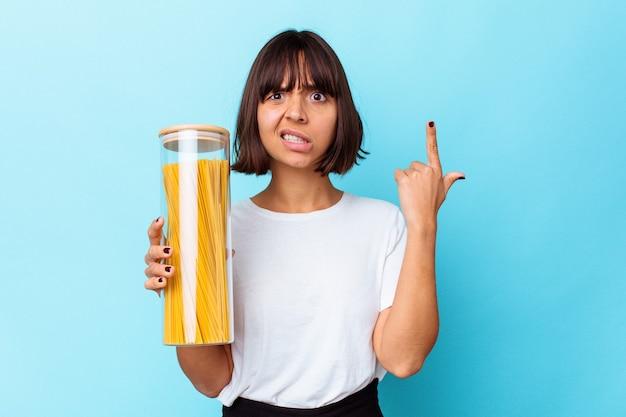 Mulher jovem de raça mista segurando o pote de macarrão isolado em um fundo azul, mostrando um gesto de decepção com o dedo indicador.