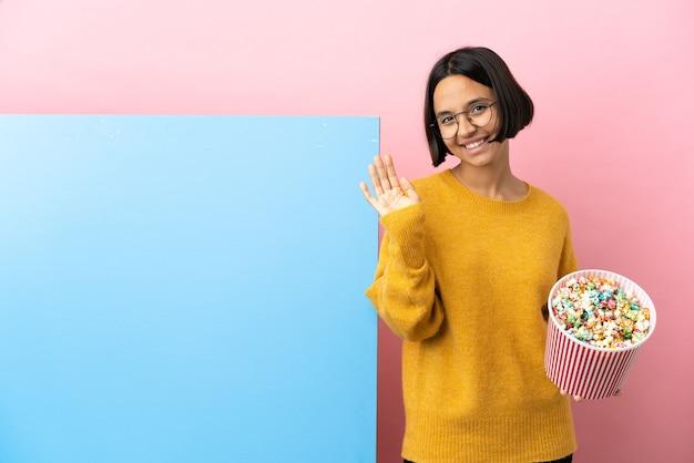 Mulher jovem de raça mista segurando pipocas com um grande banner sobre fundo isolado e saudando com a mão com expressão feliz