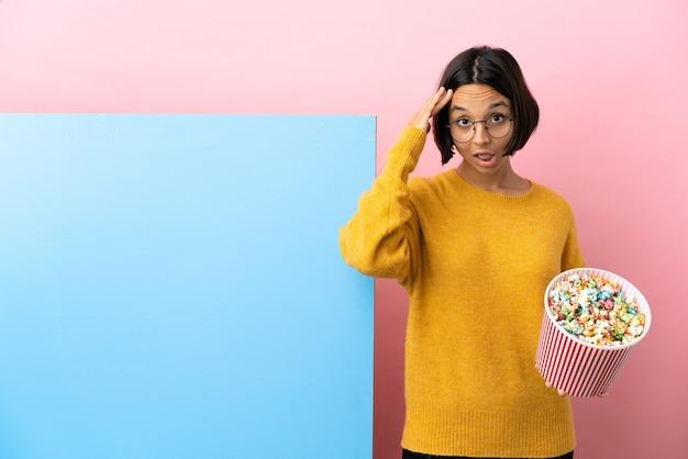 Mulher jovem de raça mista segurando pipocas com um grande banner sobre um fundo isolado com expressão de surpresa