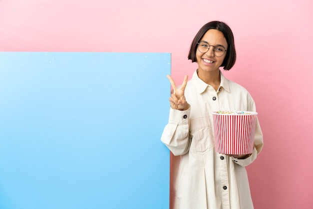 Mulher jovem de raça mista segurando pipocas com um grande banner sobre um fundo isolado sorrindo e mostrando o sinal da vitória