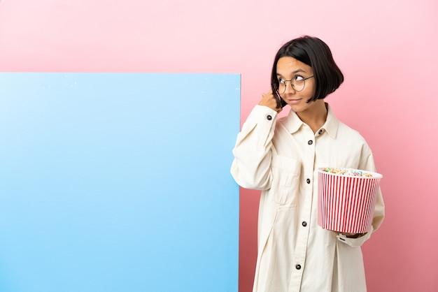 Mulher jovem de raça mista segurando pipocas com um grande banner sobre um fundo isolado, tendo dúvidas e pensando