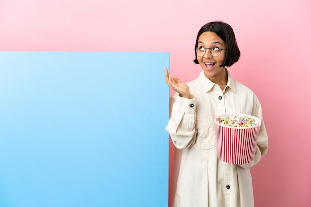 Mulher jovem de raça mista segurando pipocas com uma grande faixa sobre um fundo isolado com expressão facial surpresa