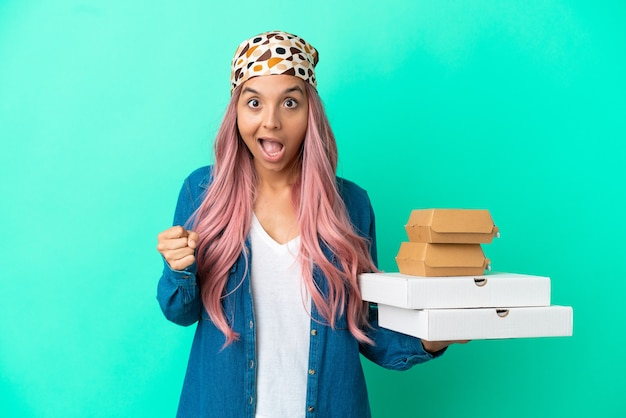 Mulher jovem de raça mista segurando pizzas e hambúrgueres isolados em um fundo verde e comemorando a vitória na posição de vencedora
