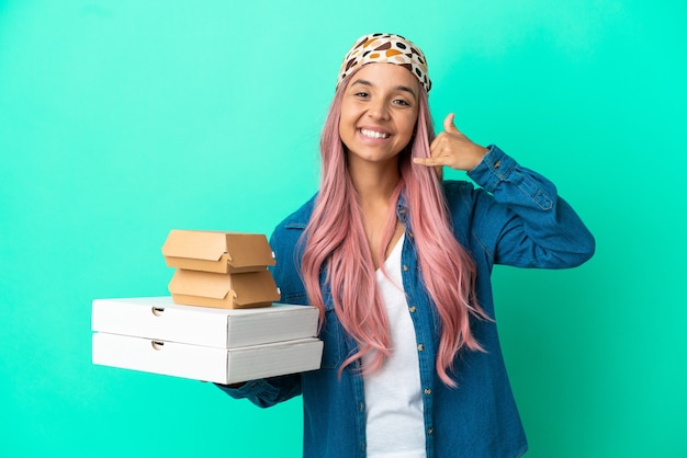 Mulher jovem de raça mista segurando pizzas e hambúrgueres isolados no fundo verde, fazendo gesto de telefone. ligue-me de volta sinal