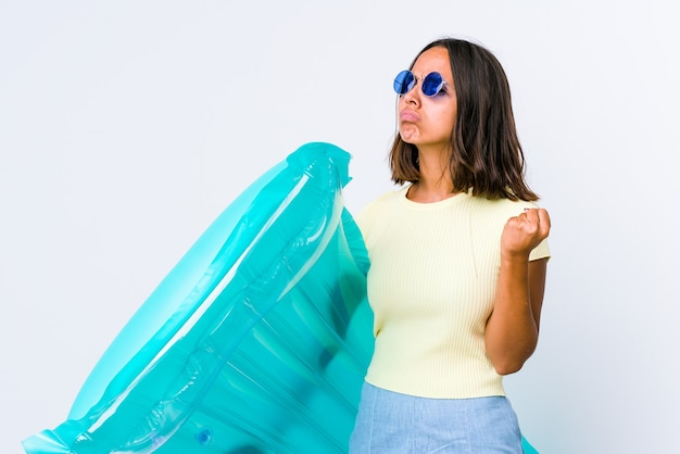 Mulher jovem de raça mista segurando um colchão de ar, mostrando o punho para a câmera, expressão facial agressiva.