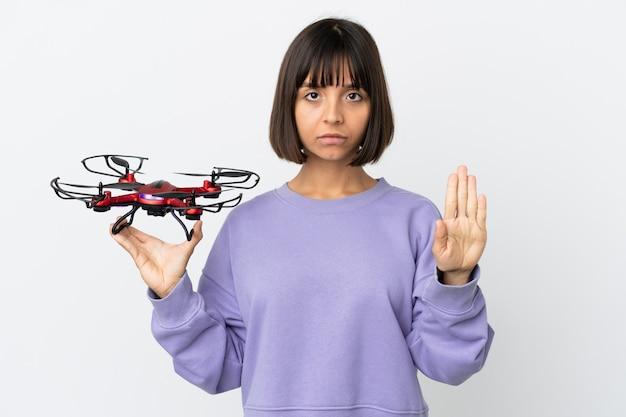 Mulher jovem de raça mista segurando um drone isolado no fundo branco fazendo gesto de pare